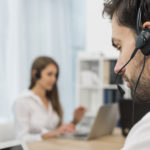 Complete managed IT services. Workers contacting customers on hands free telephone.