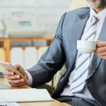 Businessman drinking coffee and checking his work smartphone.