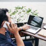 Businessman on a phone call away from the office using cloud voice services.
