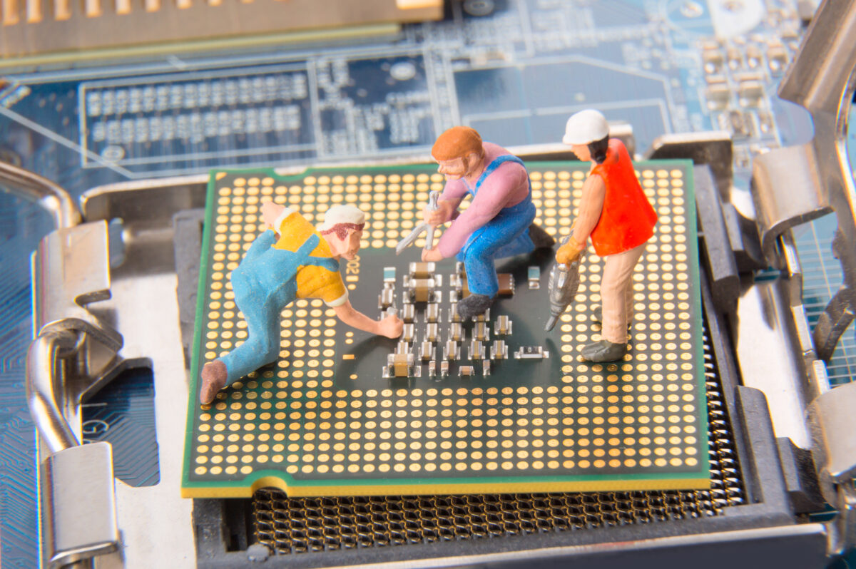 Miniature engineers or technician workers repairing CPU on the motherboard. Computer service and technology concept