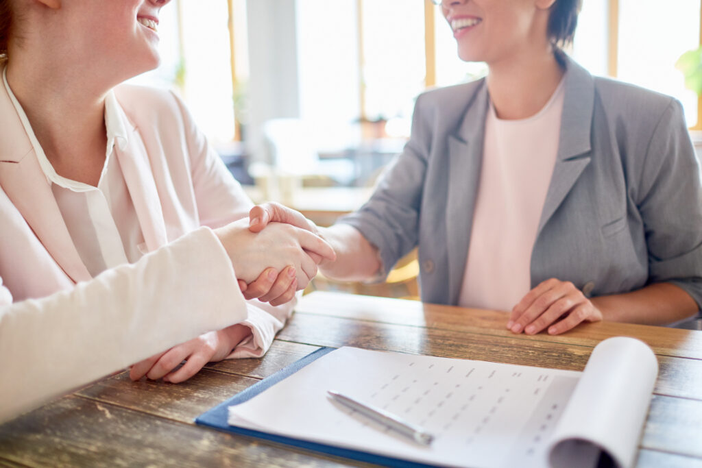 Close-up shot of unrecognizable business partners shaking hands as sign of successful negotiations, clipboard with signed documents on foreground