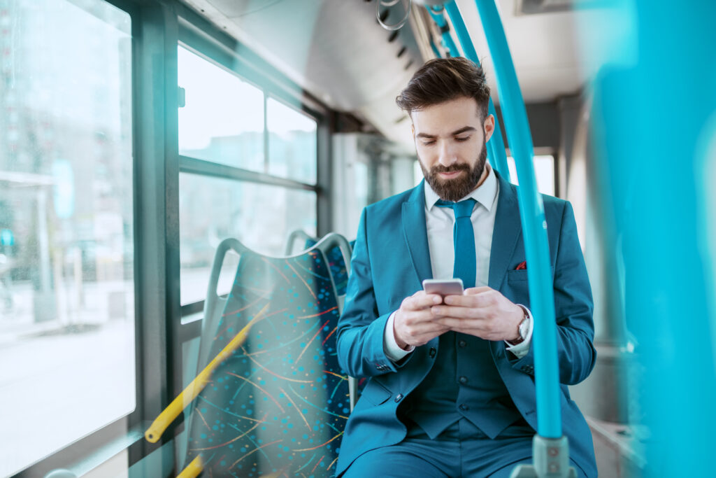 Young attractive serious Caucasian bearded businessman in blue suit sitting in public bus and using smart phone.