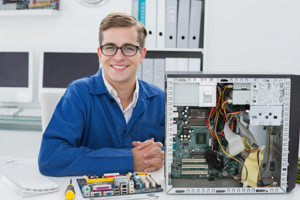 Smiling technician working on broken computer in his office - IT Support